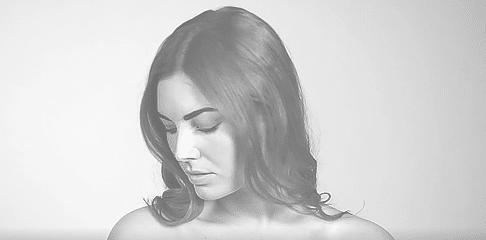 prislista - vacker kvinna - modell på MyBeauty Clinic tittar ner över sin axel