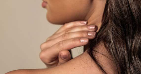 Kvinna visar sin skönhet, kvinnan tar sig på nacken